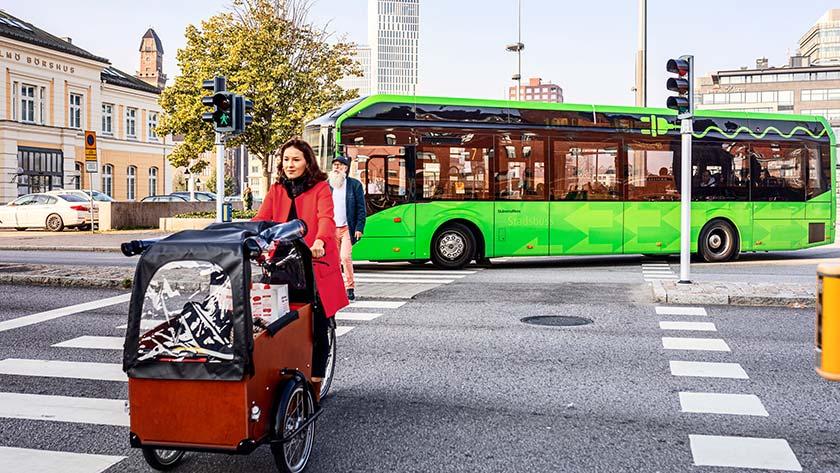 Lådcykel och buss i stadsmiljö